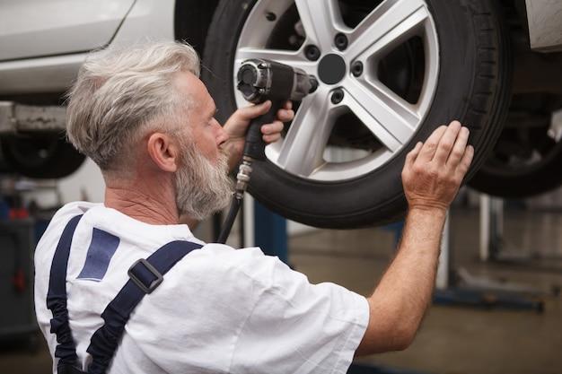 Reveja a cena de um mecânico sênior consertando as rodas de um carro no elevador