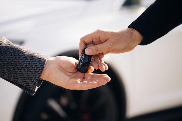Revendedor dando a chave para o novo proprietário em salão de automóveis ou salão de beleza
