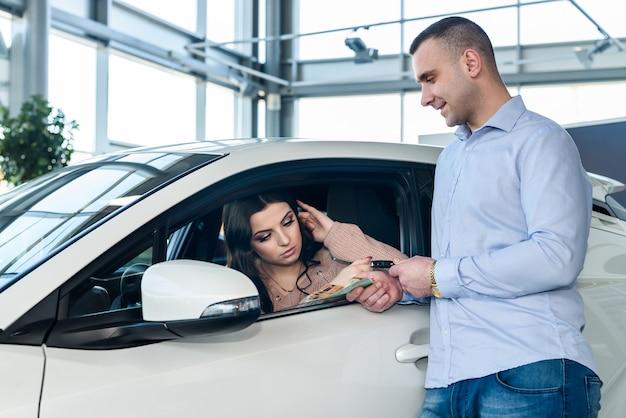 Revendedor dando chaves de carro novo para mulher bonita