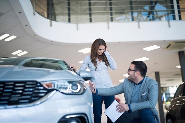 Revendedor de automóveis apresentando um carro novo ao cliente