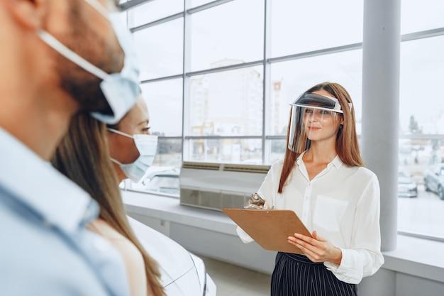 Revendedor de automóveis de mulher, consultando compradores usando protetor facial médico. conceito de requisitos de trabalho do coronavirus