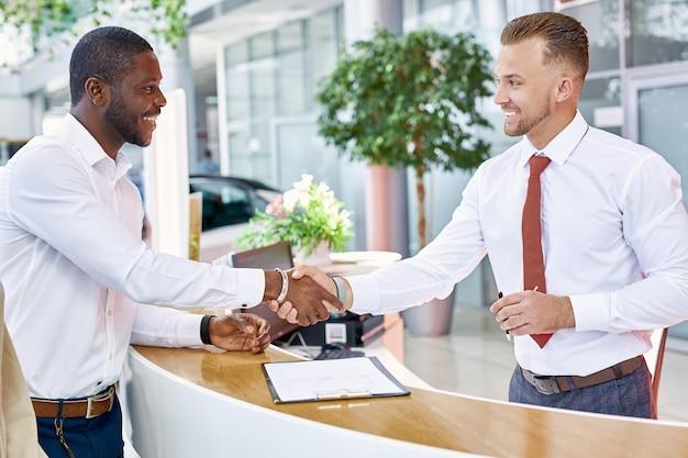Revendedor de automóveis e cliente estão apertando as mãos