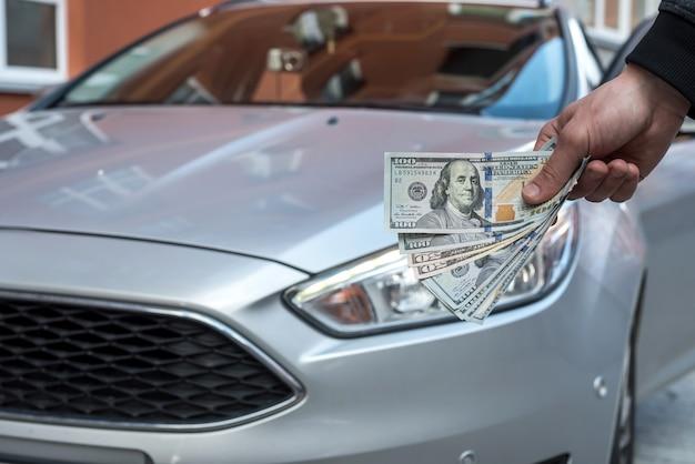 Revendedor faz acordo para comprar um novo homem de carro segurando o conceito de compra de dólar