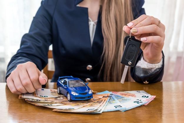 Revendedor segurando as chaves de um carro, carro de brinquedo e dinheiro em euros