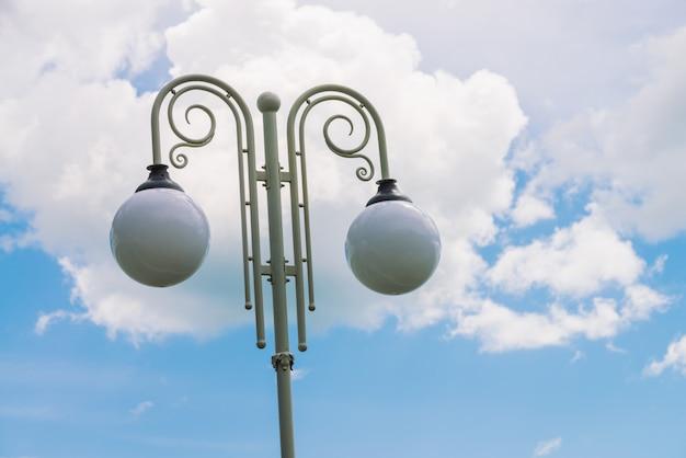 Revérbero dois esférico na coluna branca do vintage da nuvem grande no céu azul. streetlight com espaço de cópia. close de lâmpada de rua.