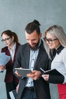 Revisão de feedback. desenvolvimento de negócios. tablet de navegação jovem sorridente líder de equipe dando instruções para a secretária.