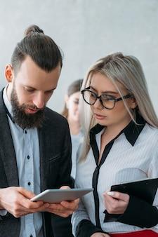 Revisão de feedback. tablet de navegação do jovem líder da equipe dando instruções para a secretária.