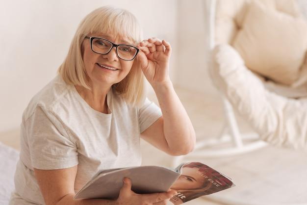 Revista de moda. mulher idosa feliz e alegre olhando para você e sorrindo enquanto lê uma revista
