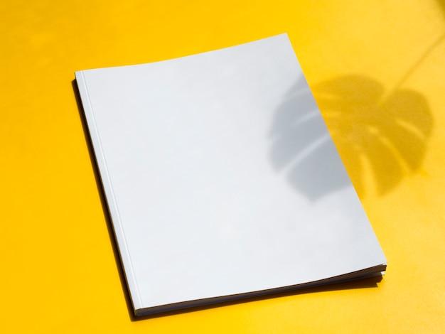 Revista em branco de close-up com fundo amarelo