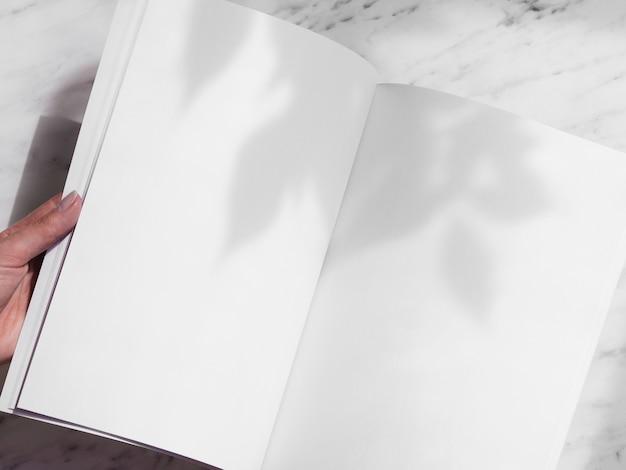 Revista em branco de close-up realizada por uma mulher