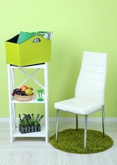 Revistas e pastas em caixa verde na prateleira e cadeira na sala