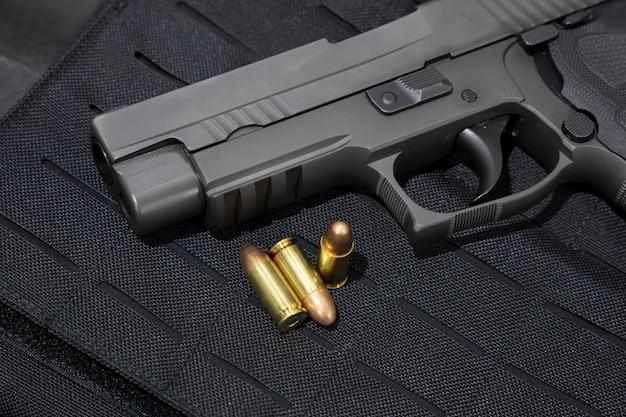 Revólver e balas de 9mm em uma jaqueta à prova de balas