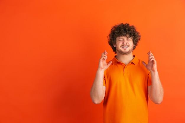 Rezando por boa sorte. retrato monocromático de jovem caucasiano na parede laranja. lindo modelo masculino encaracolado em estilo casual.