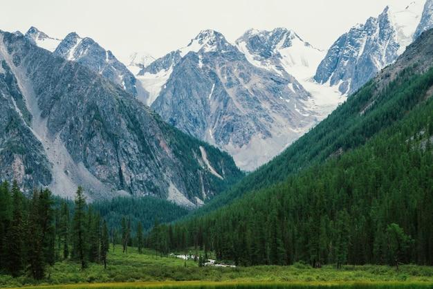 Riacho de montanha de forma serpentina no vale contra montanhas nevadas.
