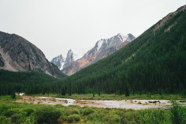 Riacho de montanha no vale contra montanhas gigantes e topos de neve.