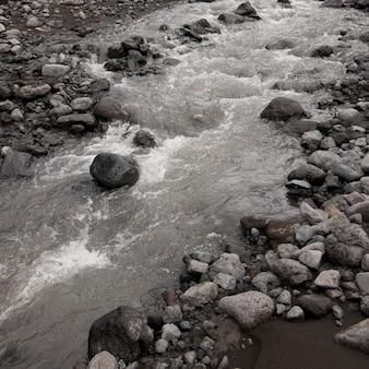 Riacho flui através do leito rochoso do rio