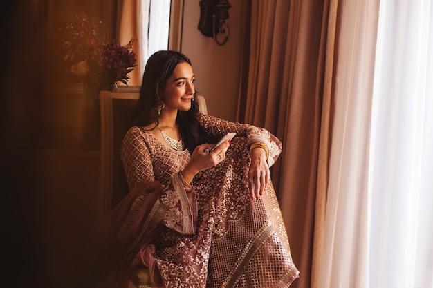 Rica e linda mulher indiana usando telefone em um quarto de hotel 5 estrelas