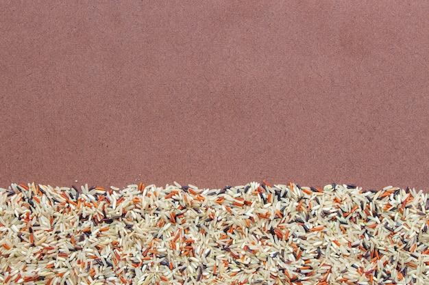 Riceberry orgânico, arroz de jasmim vermelho e arroz integral (arroz hommali) em fundo de madeira