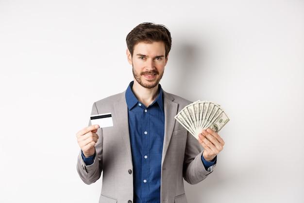 Rico e sorridente homem de terno mostrando dinheiro e cartão de crédito de plástico, em pé com notas de dólar e parece satisfeito, fundo branco.