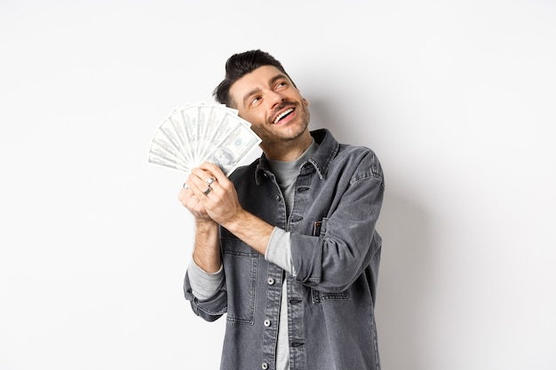 Rico feliz abraçando notas de dólar e sonhando acordado, pensando em fazer compras com dinheiro, de pé no fundo branco.