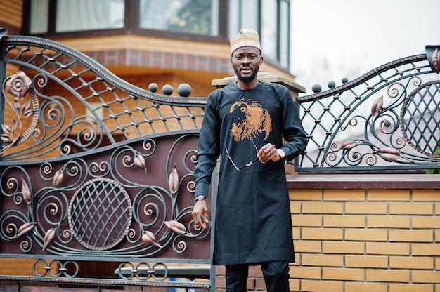 Rico homem africano em elegantes roupas tradicionais e chapéu posou ao ar livre fundo sua mansão.
