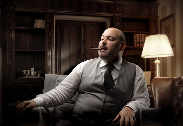 Rico homem gordo fumando um charuto