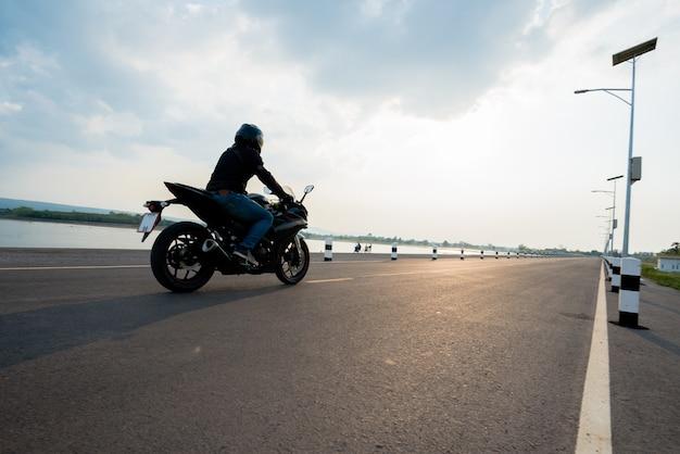 Rider motorbike na equitação da estrada. se divertindo dirigindo a estrada vazia