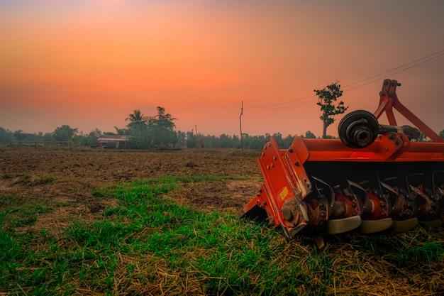 Ridging máquina de repressão. fornecimento para trator. máquinas agrícolas na fazenda agrícola. exploração agrícola do arroz na manhã com o céu vermelho do nascer do sol. natureza das terras agrícolas. cabana do fazendeiro e pólo elétrico na terra.