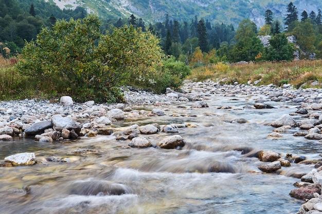 Riffle de um rio de montanha rasa em uma paisagem de outono, a água fica turva em movimento