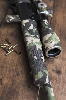 Rifle longo de pequeno calibre com mira óptica e cartuchos em fita de camuflagem