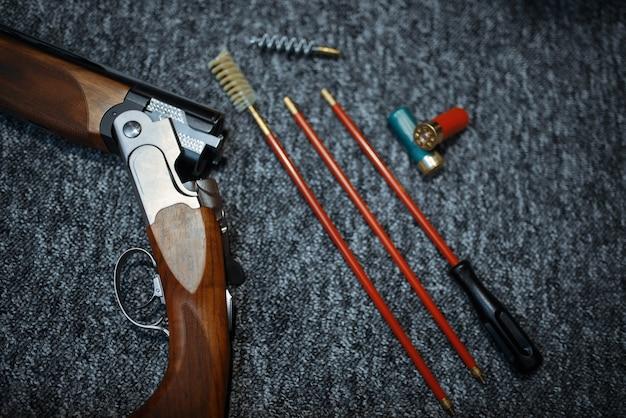 Rifle, munição e ferramentas para limpeza em loja de armas, close-up
