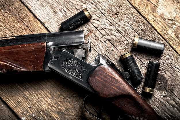 Rifle vintage e mangas na mesa de madeira