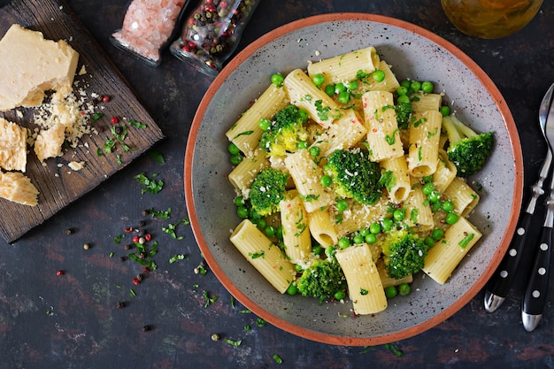 Rigatoni de massa com brócolis e ervilhas verdes. menu vegano. comida dietética. postura plana. vista do topo.