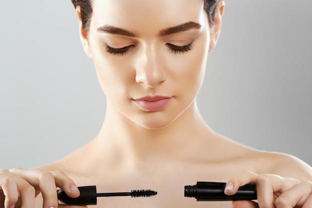 Rímel closeup de uma bela jovem, um rosto com uma maquiagem de beleza, pele macia fresca, aplicação de rímel com escova cosmética.
