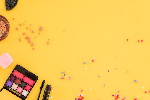 Rímel; pó facial; paleta de sombras; escova e esponja sobre fundo amarelo brilhante