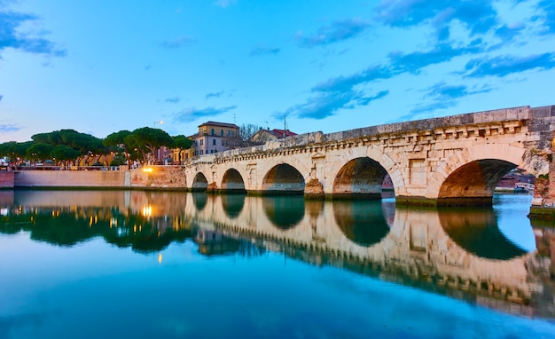 Rimini com a ponte de tibério ao entardecer, emilia-romagna, itália. paisagem com reflexo de água. arquitetura italiana