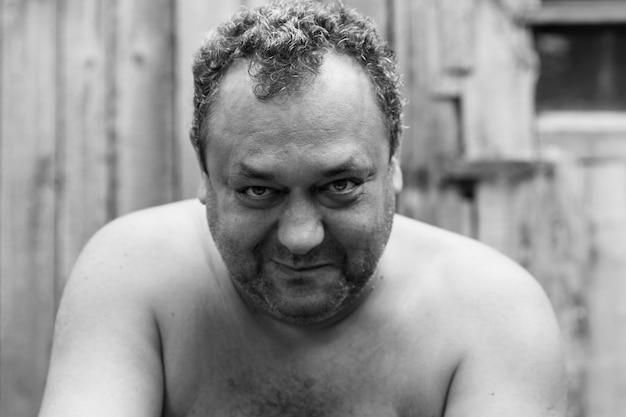 Rindo adulto alcoólatra com barba por fazer e torso nu no pátio de uma casa na aldeia. fechar-se. foto em preto e branco.