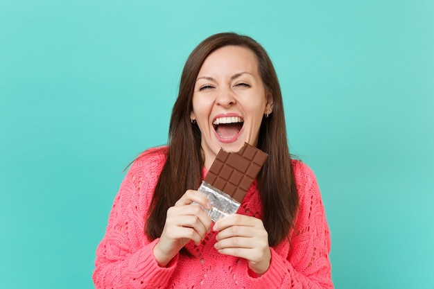 Rindo alegre jovem numa camisola de malha rosa, segurando na mão e comendo a barra de chocolate isolada no fundo da parede azul turquesa, retrato de estúdio. conceito de estilo de vida de pessoas. simule o espaço da cópia.