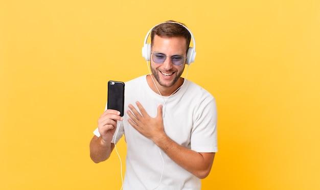 Rindo alto de alguma piada hilária, ouvindo música com fones de ouvido e um smartphone