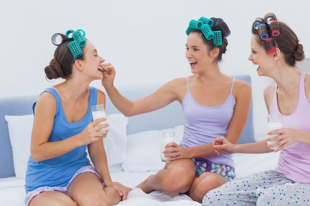 Rindo amigos sentados na cama com leite e biscoitos