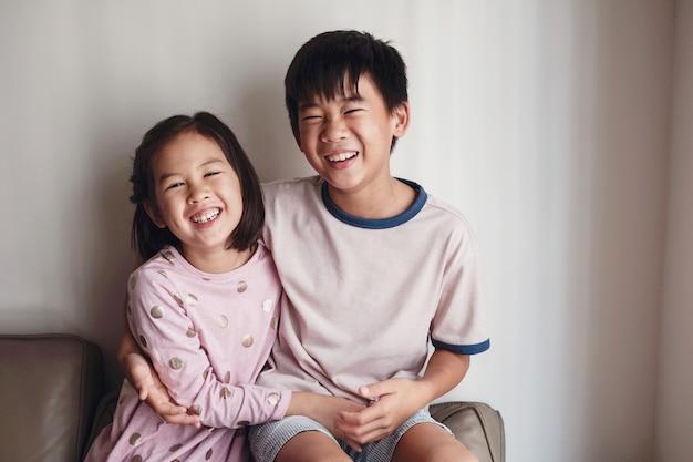Rindo asiático pequeno irmão e irmã em casa