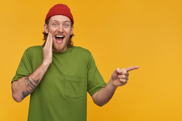 Rindo cara barbudo com cabelo loiro. vestindo camiseta verde e gorro vermelho. tem tatuagens. e apontando o dedo para a direita no espaço da cópia, isolado sobre a parede amarela