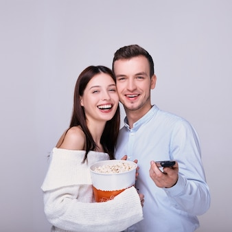 Rindo casal apaixonado com pipoca e controle remoto de tv.