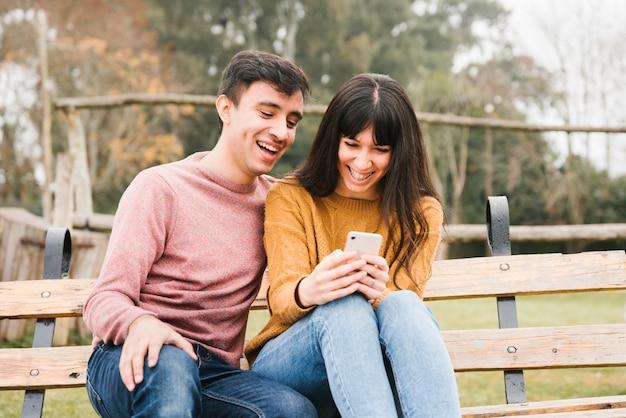 Rindo casal sentado no banco e olhando para celular