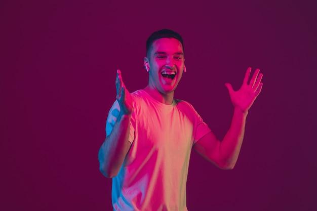 Rindo, chocado. retrato de homem branco isolado na parede rosa-roxa do estúdio.