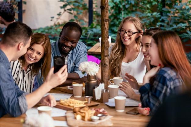 Rindo e conversando sobre a reunião pós-trabalho com colegas de trabalho no acolhedor café local