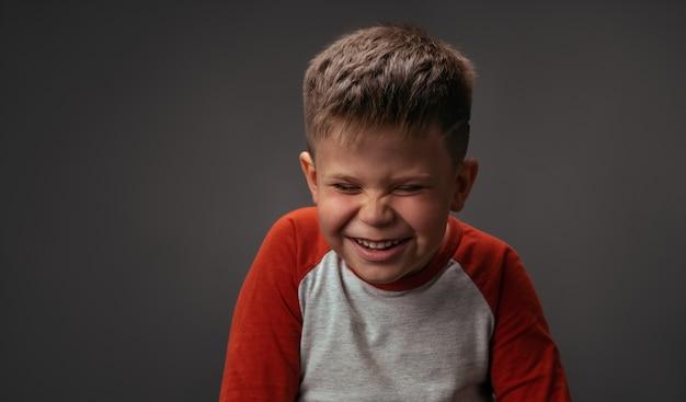 Rindo e rindo menino de camisa vermelha com os olhos fechados. criança feliz em fundo cinza escuro