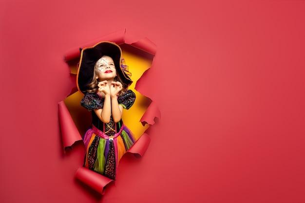 Rindo engraçado criança menina em uma fantasia de bruxa de halloween, olhando por um buraco de fundo de papel vermelho e amarelo.