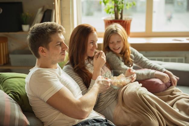 Rindo. família passando bons momentos juntos em casa, parece feliz e alegre. mãe, pai e filha se divertindo, comendo doces, assistindo tv. união, conforto do lar, amor, conceito de relações.