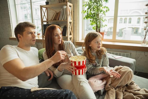 Rindo. família passando bons momentos juntos em casa, parece feliz e alegre. mãe, pai e filha se divertindo, comendo pipoca, assistindo tv. união, conforto do lar, amor, conceito de relações.